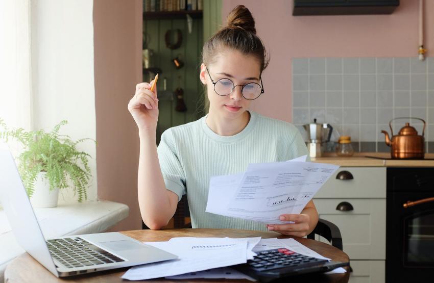 nő papírok számológép laptop konyha